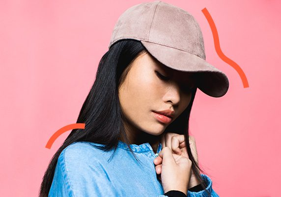 girl with baseball cap on pink background