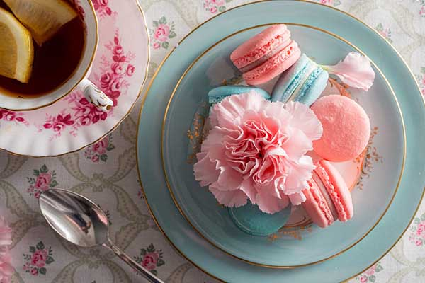Blue and pink macarons with pink carnation  served with tea in this mother's day treat setting